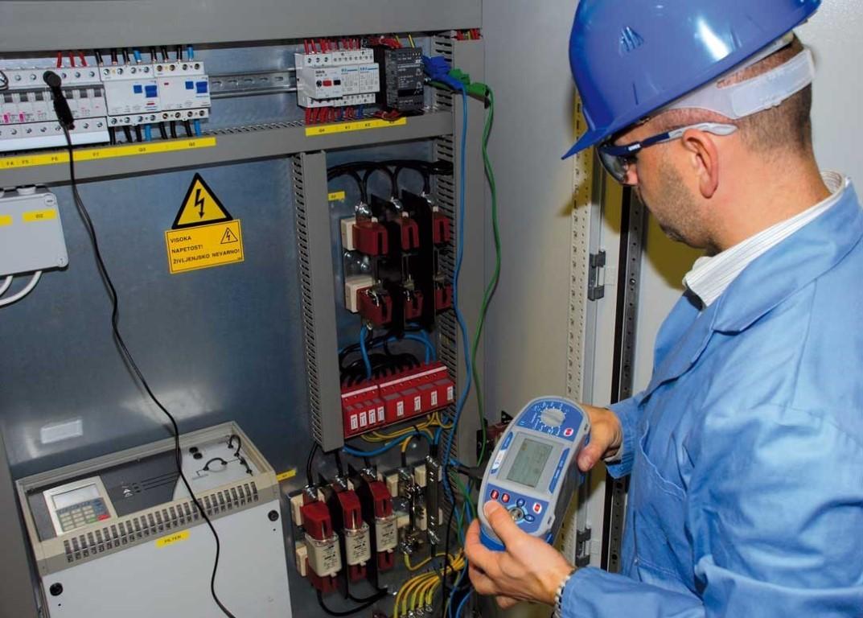 Инженер проводит замеры тока в электрощитовой