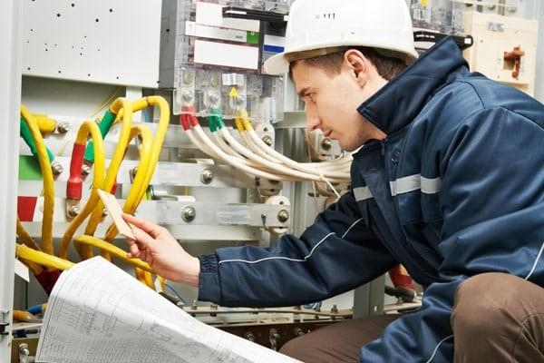 Сотрудник по электрохозяйству осматривает электрооборудование